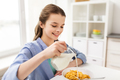 happy girl having breakfast at home kitchen