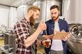 men with pipette testing craft beer at brewery