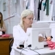 Two Women Sitting at the Tables Working on Clothing Manufacture