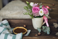 Beautiful flowers in cup on wooden background
