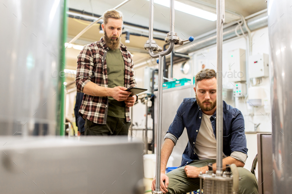 men with tablet pc at craft beer brewery filter - Stock Photo - Images