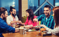 friends eating and tasting food at restaurant