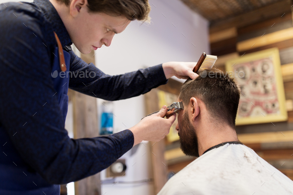 man and barber with trimmer cutting hair at salon - Stock Photo - Images