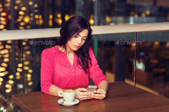woman with smartphone and coffee at restaurant - Stock Photo - Images