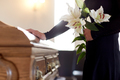 woman with lily flowers and coffin at funeral - PhotoDune Item for Sale