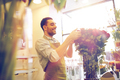 smiling florist man with roses at flower shop