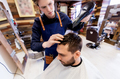 barber with fan drying male hair at barbershop