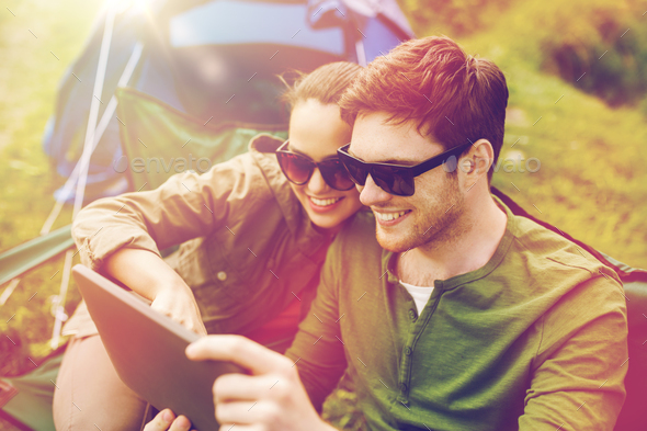 happy couple with tablet pc at camping tent - Stock Photo - Images