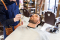 barber cleaning male face with brush at barbershop