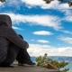 Girl in a Hoodie Sits and Contemplates the Sky - VideoHive Item for Sale
