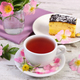 Cup of tea with cheesecake and wild rose flower on old board - PhotoDune Item for Sale