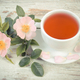 Vintage photo, Cup of tea and wild rose flower on rustic wooden background - PhotoDune Item for Sale
