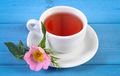 Cup of hot tea and wild rose flower on blue boards