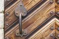 Antique door knob over a rusty wooden door. Horizontal