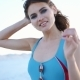 Brunette Woman in Blue Swimming Suit Shakes Her Hair Posing on the Beach - VideoHive Item for Sale