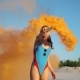 Woman in Blue Swimming Suit Plays with Orange Smoke on the Beach - VideoHive Item for Sale
