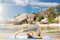 woman doing yoga in plow pose on beach