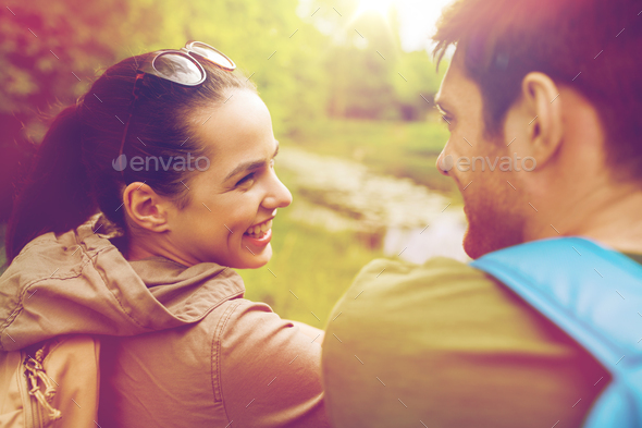 smiling couple with backpacks in nature - Stock Photo - Images