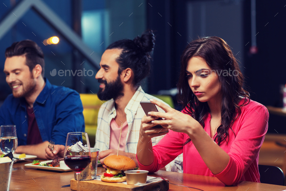 woman with smartphone and friends at restaurant - Stock Photo - Images
