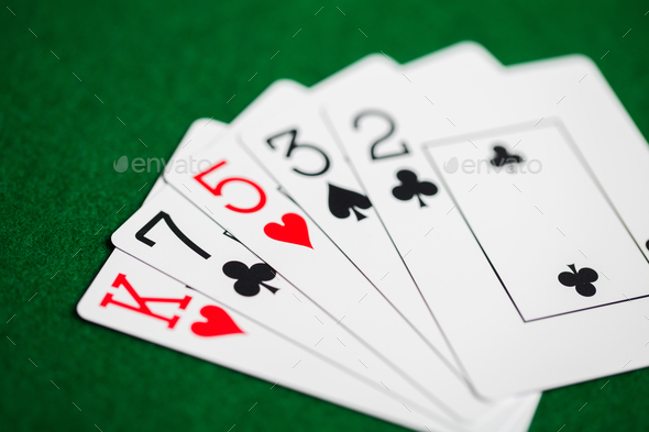poker hand of playing cards on green casino cloth - Stock Photo - Images