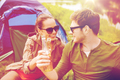 happy couple clinking drinks at campsite tent
