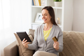 happy woman with tablet pc and bank card at home