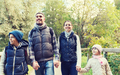 happy family with backpacks hiking in woods