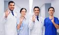 group of medics at hospital showing ok hand sign