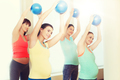 happy pregnant women exercising with ball in gym