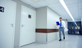 doctor with clipboard walking along hospital