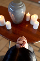 sad woman with funerary urn praying at church