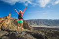 Hiking or climbing success with arms raised in mountains