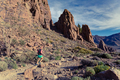 Woman running in mountains on rocky trail