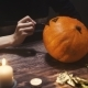 Young womanDrawing Eyes and Mouth on Halloween Pumpkin To Carve a Jack 'O' Lantern. The Winter