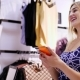 Sexy Girl, Beautiful Blond Woman Shopping in a Store, Boutique Clothes She Smiles, Holds a Mobile