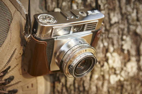 Old fashioned film camera detail and hiking boots. Travel background - Stock Photo - Images