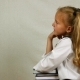 School Girl in Uniform Sits Elbows on Books and Smiling at Camera. Side View - VideoHive Item for Sale