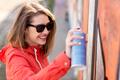 teenage girl drawing graffiti with spray paint