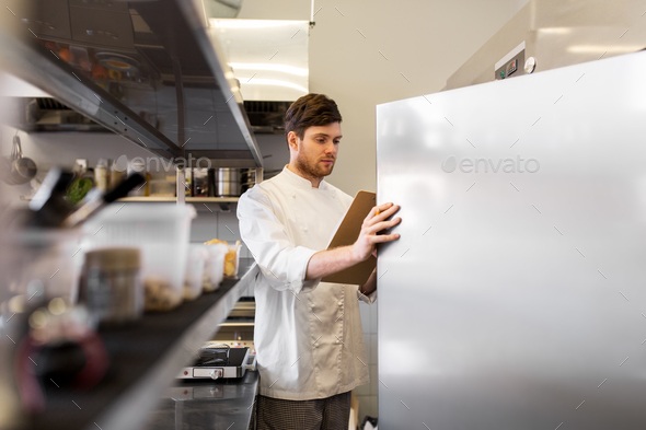 chef with clipboard doing inventory at kitchen - Stock Photo - Images