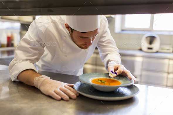male chef decorating dish with pansy flower - Stock Photo - Images