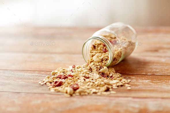jar with granola or muesli poured on table - Stock Photo - Images