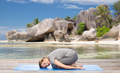 happy woman doing yoga in child pose on beach