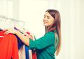 happy woman choosing clothes at home wardrobe