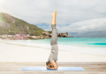 woman doing yoga in headstand pose on beach