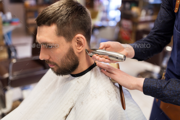man and barber hands with trimmer cutting hair - Stock Photo - Images