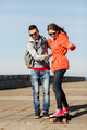happy couple with longboard riding outdoors