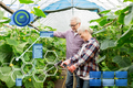 senior couple with garden hose at farm greenhouse