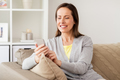 happy woman texting message on smartphone at home