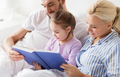 happy family reading book in bed at home