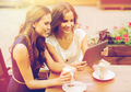 young women with tablet pc and coffee at cafe